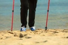 Nordic supérieur de femme active marchant sur une plage pattes Photo stock