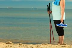 Nordic superior da mulher ativa que anda em uma praia pés Fotografia de Stock