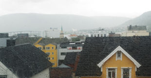 Nordic town Tromso through the wet window glass. Royalty Free Stock Photo
