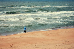 Nordic walker on the beach. Woman on the beach. Nordic walker on the beach with stormy sea Royalty Free Stock Photography