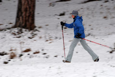 Nordic walking. Woman walking with poles, intentional motion blur Stock Photos