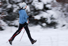 Nordic walking. Woman walking with poles, intentional motion blur royalty free stock photography