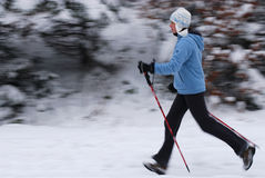 Nordic walking. Woman walking with poles, intentional motion blur Stock Image