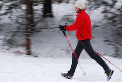 Nordic walking. Woman walking with poles, intentional motion blur Royalty Free Stock Photo