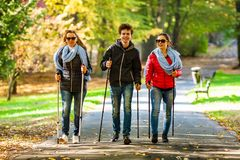 Nordic walking - active people working out. In park Stock Image
