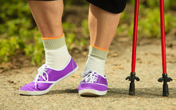 Nordic walking. Closeup of mature female legs Royalty Free Stock Photos