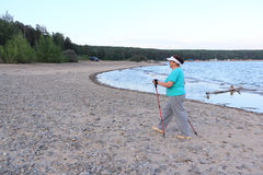 Nordic Walking - elderly woman is hiking along the river Royalty Free Stock Photo