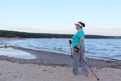 Nordic Walking - elderly woman is hiking along the river Stock Photography