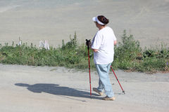 Nordic Walking - elderly woman is hiking  in the summer Royalty Free Stock Photography