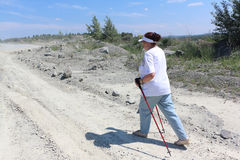 Nordic Walking - elderly woman is hiking  in the summer Royalty Free Stock Photos