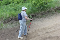 Nordic Walking-elderly woman in a striped blouse going uphill Stock Image