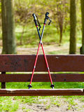 Nordic walking equipment on the park bench. Royalty Free Stock Photo