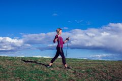 Nordic walking, exercise, adventure, hiking concept -a woman hiking in the nature royalty free stock image