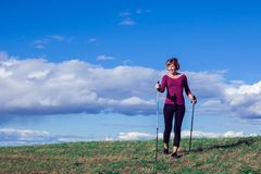 Nordic walking, exercise, adventure, hiking concept -a woman hiking in the nature royalty free stock photos