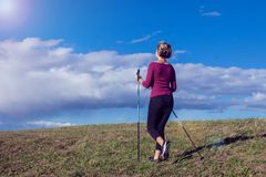 Nordic walking, exercise, adventure, hiking concept -a woman hiking in the nature stock photo