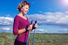 Nordic walking, exercise, adventure, hiking concept -a woman hiking in the nature royalty free stock photography
