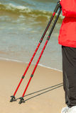 Nordic walking. Female legs hiking on the beach. Stock Image