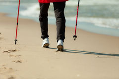 Nordic walking. Female legs hiking on the beach. Royalty Free Stock Images