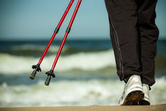 Nordic walking. Female legs hiking on the beach. Royalty Free Stock Image