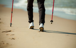 Nordic walking. Female legs hiking on the beach. Nordic walking. Closeup of female legs hiking on the beach. Active and healthy lifestyle Stock Image