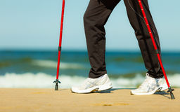 Nordic walking. Female legs hiking on the beach. Royalty Free Stock Photo