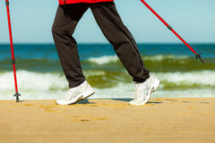 Nordic walking. Female legs hiking on the beach. Royalty Free Stock Photography