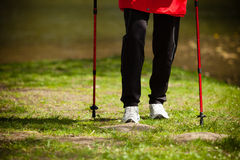 Nordic walking. Female legs hiking in the park. Royalty Free Stock Photography