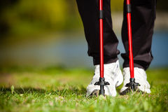 Nordic walking. Female legs hiking in the park. Stock Image