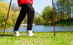 Nordic walking. Female legs hiking in the park. Royalty Free Stock Photos