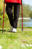 Nordic walking. Female legs hiking in the park. Stock Photo