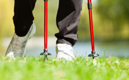 Nordic walking. Female legs hiking in the park. Stock Photos
