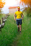 Nordic walking in the grass with sticks in hand Stock Photo