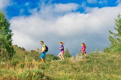 Nordic walking instructor with two girls on mountain trail.  Stock Photos