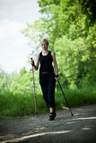 Nordic walking in nature. Nordic walking in summer nature. Woman exercise Royalty Free Stock Images