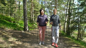 Two active women do Nordic walking in the Park. Tracking shot. Nordic walking outdoor activity for all ages. Two active women working out in the Park. Tracking stock video footage