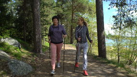 Two active women do Nordic walking in the Park. Tracking shot. Nordic walking outdoor activity for all ages. Two active women working out in the Park. Tracking stock footage
