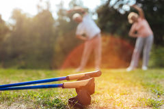 Nordic walking poles lying on the ground. Nordic walking equipment. Nordic walking poles lying on the ground with active sporty senior couple exercising in the Royalty Free Stock Photos