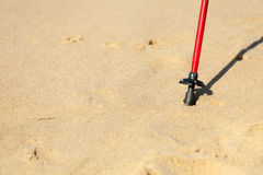 Nordic walking. Red stick on the sandy beach Stock Images
