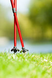 Nordic walking. Red sticks on grass in park Royalty Free Stock Photography
