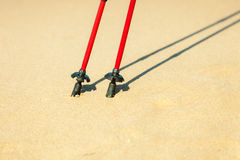 Nordic walking. Red sticks on the sandy beach Royalty Free Stock Photos