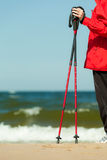 Nordic walking. Red sticks on the sandy beach Stock Photo