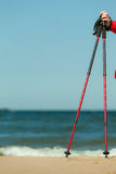 Nordic walking. Red sticks on the sandy beach Royalty Free Stock Photo