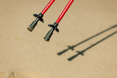Nordic walking. Red sticks on the sandy beach Royalty Free Stock Images