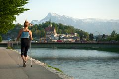 Nordic walking in Salzburg at the Salzach river in the city, promenade stock photo