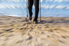 Nordic walking sport run walk motion blur outdoor person legs se. Feet of man cultivating Nordic walking on the beach Royalty Free Stock Photos