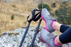 Nordic walking sticks near female legs Royalty Free Stock Photo