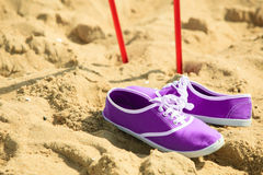 Nordic walking. sticks and violet shoes on a sandy beach Royalty Free Stock Photos