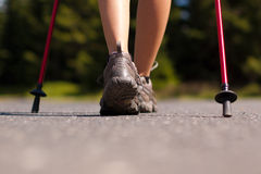 Nordic walking in summer. Closeup of woman's legs with nordic walking poles Royalty Free Stock Photos