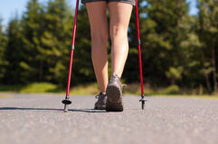 Nordic walking in summer. Closeup of woman's legs with nordic walking poles Royalty Free Stock Photo