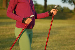 Nordic walking in summer. Closeup of man's legs with nordic walking poles Stock Photography